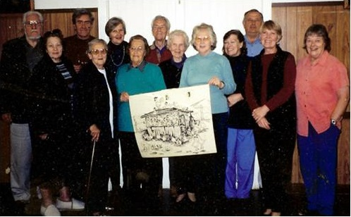 Group of people standing, 2 people at front holding a drawing.
