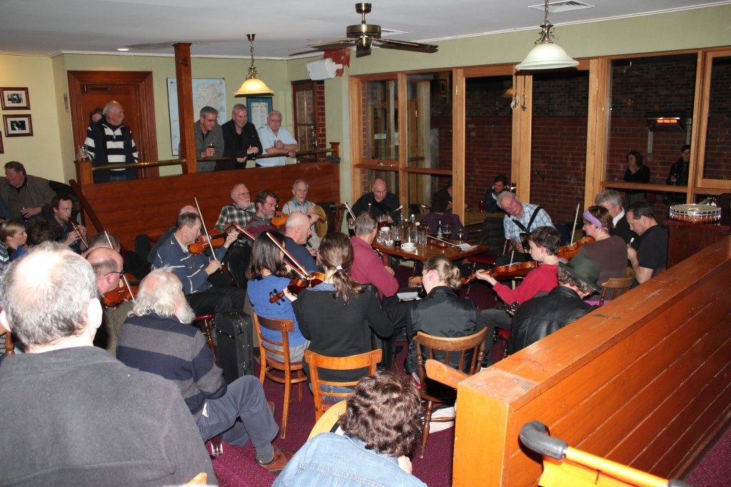 A small group of people playing violins at the Corkman
